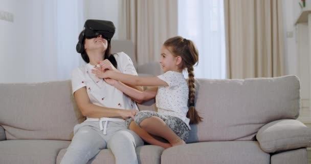 Mom and daughter spending a nice time together mother using a virtual reality glasses to exploring a new world , while sitting in the sofa