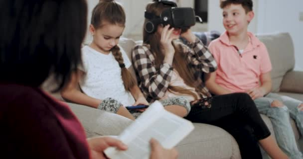 A old woman granny reading a book on the sofa while her grandchildren playing in a virtual reality glasses they have a great time together