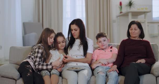 Tři generace babičky Dcera a vnoučata, kteří se dívají na televizi a jedí sušenky před kamerou na pohovce, mají atraktivní obličeje.