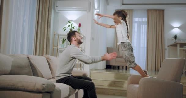 Charismatická malá holčička trávila zábavu se svým otcem v prostorných obývacím pokoji a vyskočila na tátu, zatímco sedí na pohovce