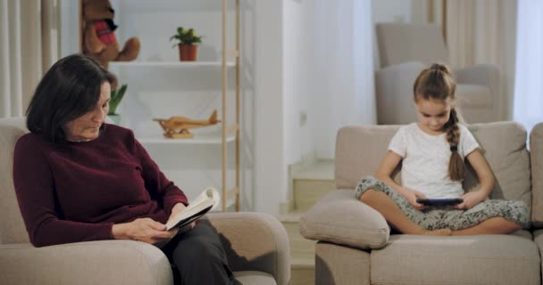 Beautiful granny with her niece spending a time together in living room granny reading a book on the couch and niece playing a game on the smartphone while sitting on the sofa. 4k
