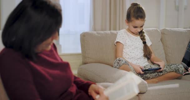 Closeup charismatická babička četla knihu soustředěnou, zatímco její neteř hrála hru na telefonu, který sedí na pohovce. 4k