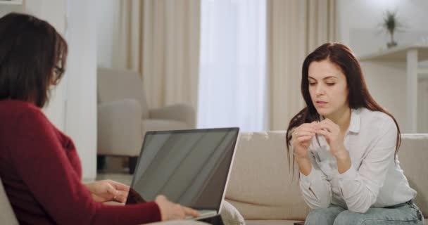 A pszichológus beteg nő egy terápia elmondja róla a mentális egészség és a feldúlt arcát, orvos gépelés rajta notebook néhány információt a problémáról