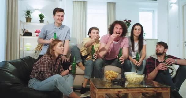 Egy nagy tágas nappali egy baráti csoport több etnikai boldog élvezi az időt együtt, hogy van egy videojáték idő két hölgy játszik a PSP, míg a többi barátok italok sör és