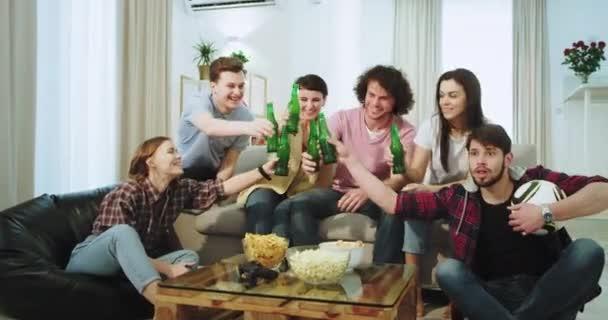 Sehr enthusiastische Freunde Jungs und Damen genießen die Zeit zusammen vor der Kamera beobachten ein Fußballspiel und unterstützen ihre beste Mannschaft trinken Bier und jubelt mit Flaschen