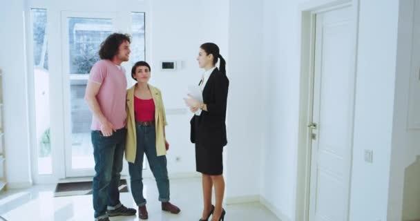 Ve světélkující moderní budově s realitním agentem, která se v domě ukazuje svým klientům přitažlivým mladým párem, analyzují domovní plán skrz tablet