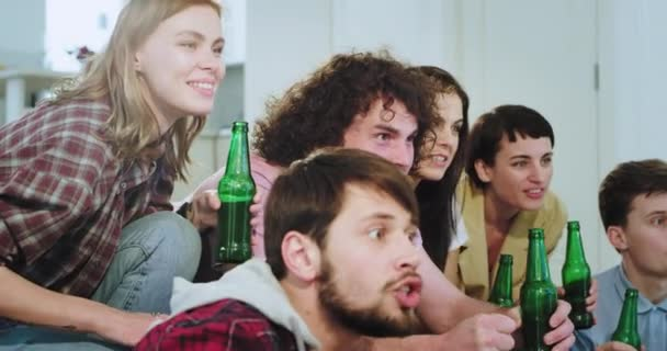 In a modern house group of friends multi ethnic watching very emotional a football match they happy celebrating first goal of their team yelling clapping hands and cheers with beer bottles very