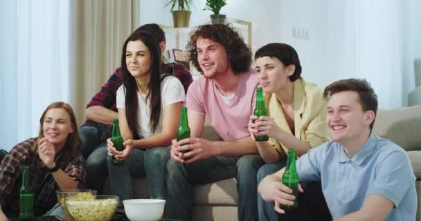 lächelnde große, charismatische Freunde, die gemeinsam auf dem Sofa ein Fußballspiel verfolgen und ihre Mannschaft unterstützen, während sie Bier trinken.