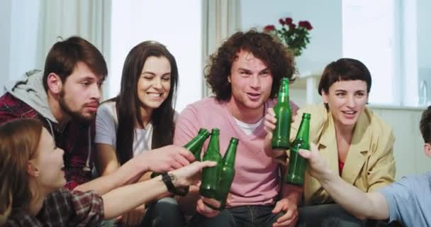 Portrait of a big company very attractive friends smiling large while watching the football match very excited they cheers with a beers bottle and celebrating the goal
