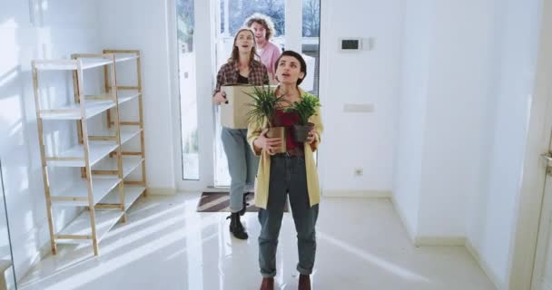 Charismatic and attractive couple and their friends moving to a new house very impressed and excited they holding big boxes and flowers, modern house interior