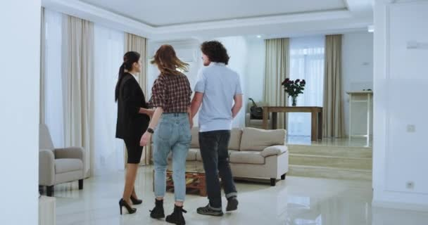 In a spacious large house young married couple and attractive real estate agent representing the new house for the client they are very excited and impressed