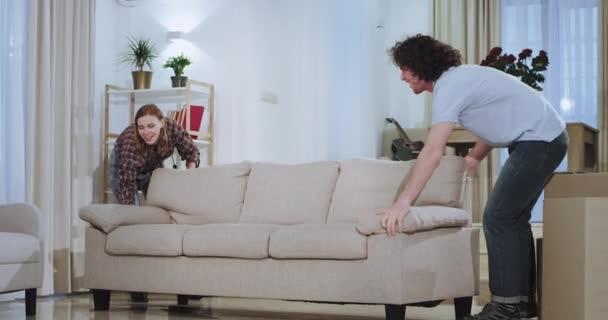 Mladý atraktivní pár těší čas v novém domě přesunuli pohovku uprostřed obývacího pokoje poté, co vzrušeni objímají jeden druhého