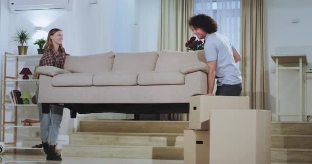 Moving day for attractive young couple they carrying the sofa in the middle of a spacious living room happy they enjoy the moment together in a new house