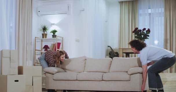 Egy nagy tágas nappali karizmatikus pár kezében egy nagy kanapé a nappaliban élvezi az időt egy új házat, amikor költözött boldog vesznek egy ül a kanapén, és egy kis szünetet, miközben