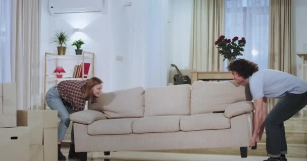 Attractive guy with his girlfriend moved in a new apartment they make some changes carrying the sofa in the middle of living room they excited take a sit on the sofa and start to watch the TV.