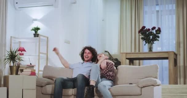 Velmi šťastný a charismatický pár v novém domě se pohnul a nesl velké krabice do obývacího pokoje, kde seděli na pohovce a odpočívali