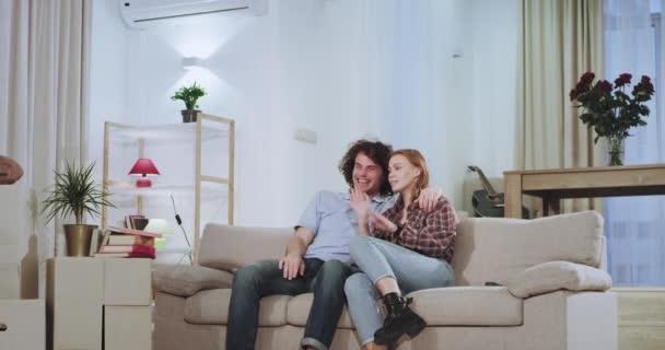 A mosolygó és izgatott pár élvezi az időt egy új lakásban után egy kemény mozgó nap vesznek a távoli TV-től, és kapcsoljuk be, hogy néz valamit, és egy pihentető idő