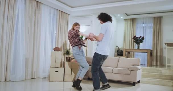 tanzt ein sehr attraktives Paar in einem neuen Haus und genießt die gemeinsame Zeit glücklich und sehr aufgeregt nach einem bewegenden Tag