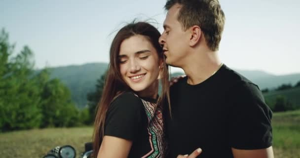 Portrait of a young couple touching romantic each other in amazing landscape place beside of their motorcycle