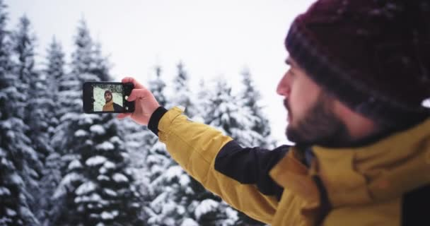 Selfie time for a young charismatic tourist in the mountain found amazing snowy forest and very elated take pictures