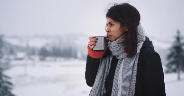 Podrobnosti o šatně mladá dáma s teplým oblečením a stojící na vrcholu hory si Připijme horký nápoj z železného šálku