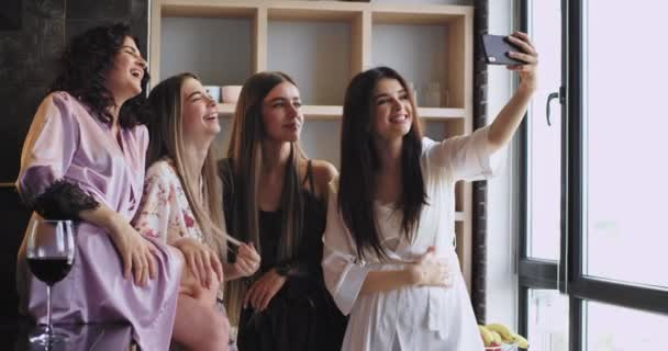 Multi ethnic beautiful ladies with a beautiful smile take selfies with a smartphone in pajamas in a urban design studio , celebrating bachelorette party