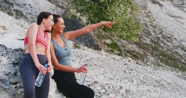Usmívající se atraktivní dvě mladé ženy, které si spolu užívají čas v přírodě po sportovní rutině, kdy si vychutnávají čas v čerstvém vzduchu a popíjí ještě vodu