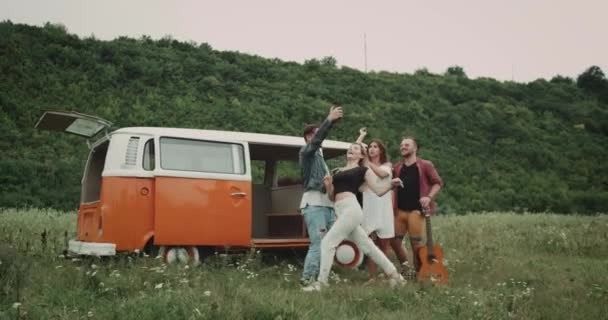 At the picnic pretty couples taking selfies , have a good mood , behind them stand a retro van.