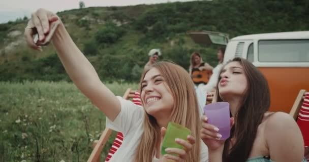 Nahaufnahme zwei charismatische Damen, die beim Picknick lächeln und Fotos machen, bunte Gläser in der Hand, im Hintergrund ein Freund, der an der Gitarre spielt, auf der Rückseite eines Retro-Transporters sitzend.
