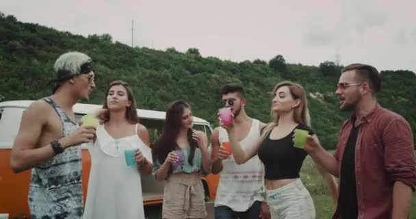 Group of young friends spending a great time together at nature , drinking from colorful glasses , happy faces, background vintage van.