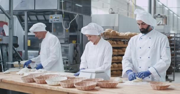 Professional bakers forming pieces of dough to baking bread on a big table in commercial kitchen industry