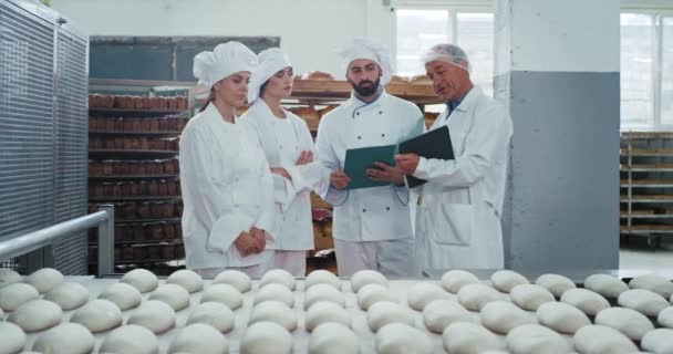 Group of manufacturing workers and engineer checking the quality of production old engineer holding a map of some notes , bakers are listing carefully