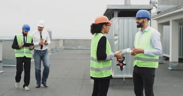Group of workers in a construction site engineer architect businessmen have a meeting on the rooftop of construction site wearing a safety helmet they holding hands and start chatting