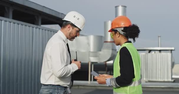 gut aussehende Ingenieurin und reifen Mann Ingenieur Analyse des Plans für den Bau auf dem Dach der Baustelle tragen sie eine Sicherheitsausrüstung und Business-Kleidung sprechen auf Ration