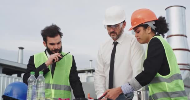 Group of construction team businessman architect and engineer analyzing the construction plan of building , they wearing a safety helmets and safety glasses