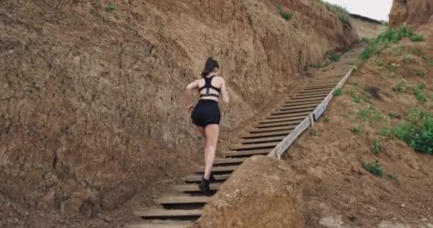 Daleko od mladé ženy v černém sportovním náčiní, běžící schody