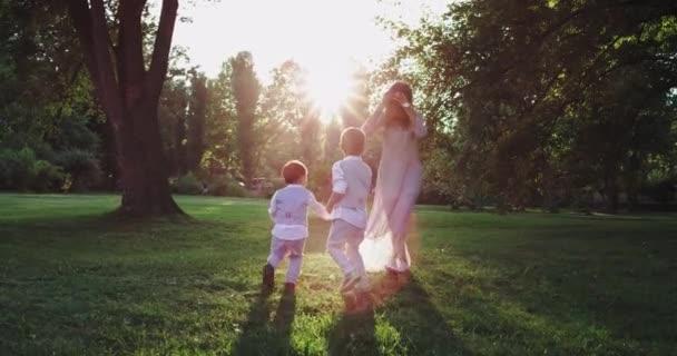 Šťastná matka si krásně zahrává s malými stylovými chlapci uprostřed parku s důkladnou krásnou zelenou trávou