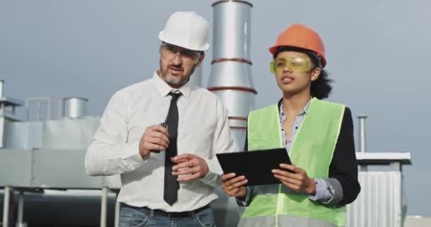 Starší hezký bílý architekt se dívá na zářící smíšenou stavební ženu, ukazuje na ni a ukáže jí místo, pak vytáhl svůj vysílač a promluví.
