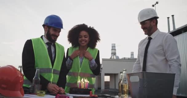 Afrikai hölgy élvezi születésnapi partiján a munka fúj a gyertyák a tetőn építkezési telek kollégáival két építészek ember