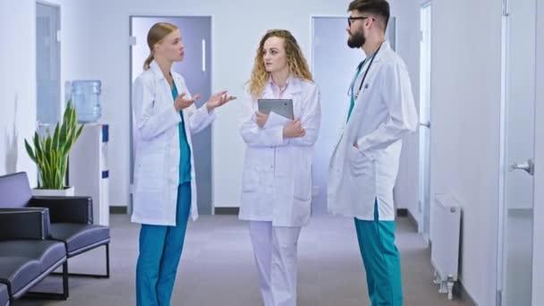 Auf dem Krankenhausflur diskutieren eine Krankenschwester und zwei Ärzte vor der Kamera über die Diagnostik des Patienten und die zukünftige Behandlung