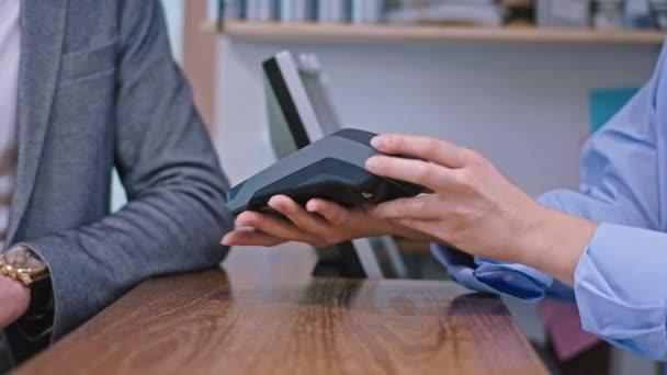 Egy modern üzletben az eladó megadja az ügyfélnek a terminált, hogy hitelkártyával fizessen.