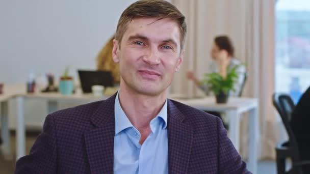 Portrét kancelářského jeslí na jeho pracovišti dívá přímo do kamery a dělat šťastný obličej při práci v moderní kanceláři