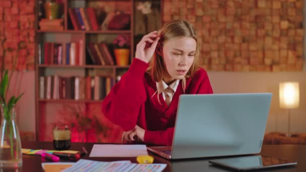 Blonde lady student doing her college project using the laptop she write something on the paper