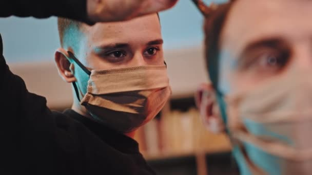 Pandemic of Coronavirus 2019 professional hairdresser closeup to the camera with protective mask doing a haircut to the client as well with protective mask