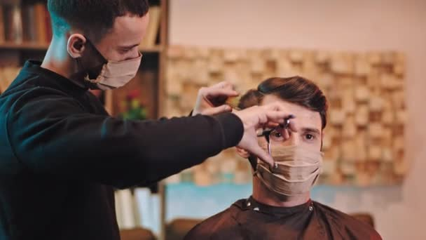 Charismatic guy with protective mask and barber man with protective mask doing a hair cut in the quarantine at home Covid-19. 4k