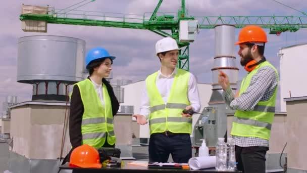 Auf der Baustelle tragen eine Assistentin und ein Ingenieur auf dem Dach des Gebäudes, die den nächsten Bauplan analysieren, Schutzhelme