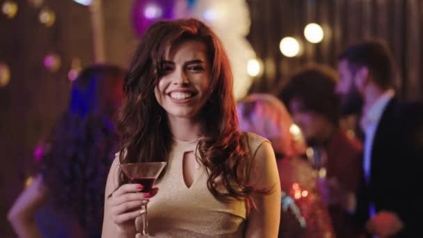 Auf einer Geburtstagsparty genießt junge Frau vor der Kamera die Nacht, die sie so aufgeregt erlebt und beginnt zu feiern
