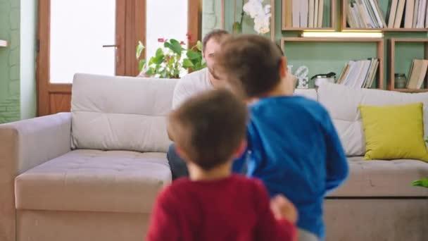 Na pohovce atraktivní muž a dáma si sednout a čekat na své děti přicházejí a objímají krásné maminku a tatínka si užívají domácí atmosféru