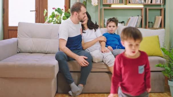 Mladí rodiče tráví dobrý čas se svými dětmi, usmívají se, klábosí a objímají se, zatímco sedí na pohovce