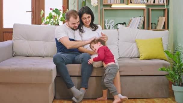 Mladí rodiče mají krásný čas se svým dítětem, které se usmívá velké a en čas doma, zatímco sedí na pohovce